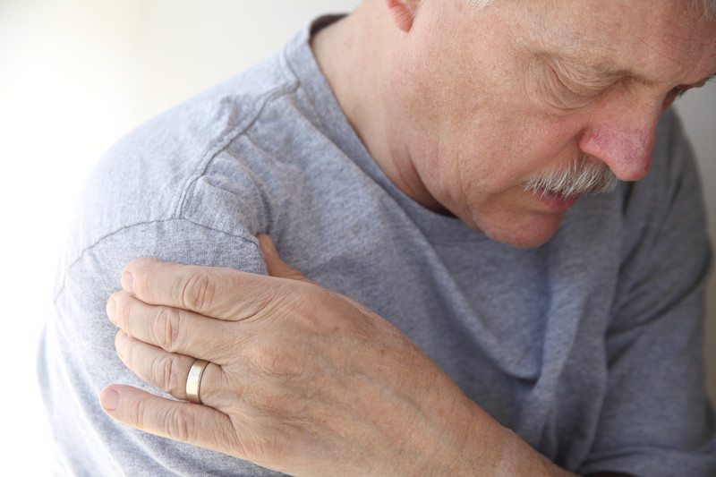 bursitis pain man holding shoulder