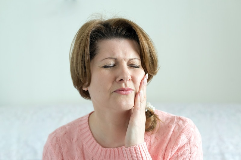 woman with pain in lower jaw due to TMJ Dysfunction